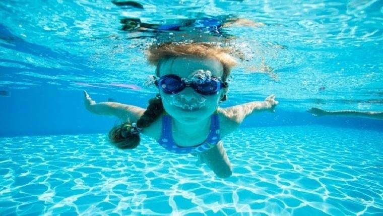 プールで女の子がゴーグルをかけて潜っている