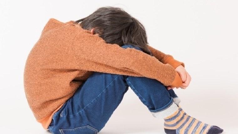 男の子が膝を抱えて悩んでいる写真